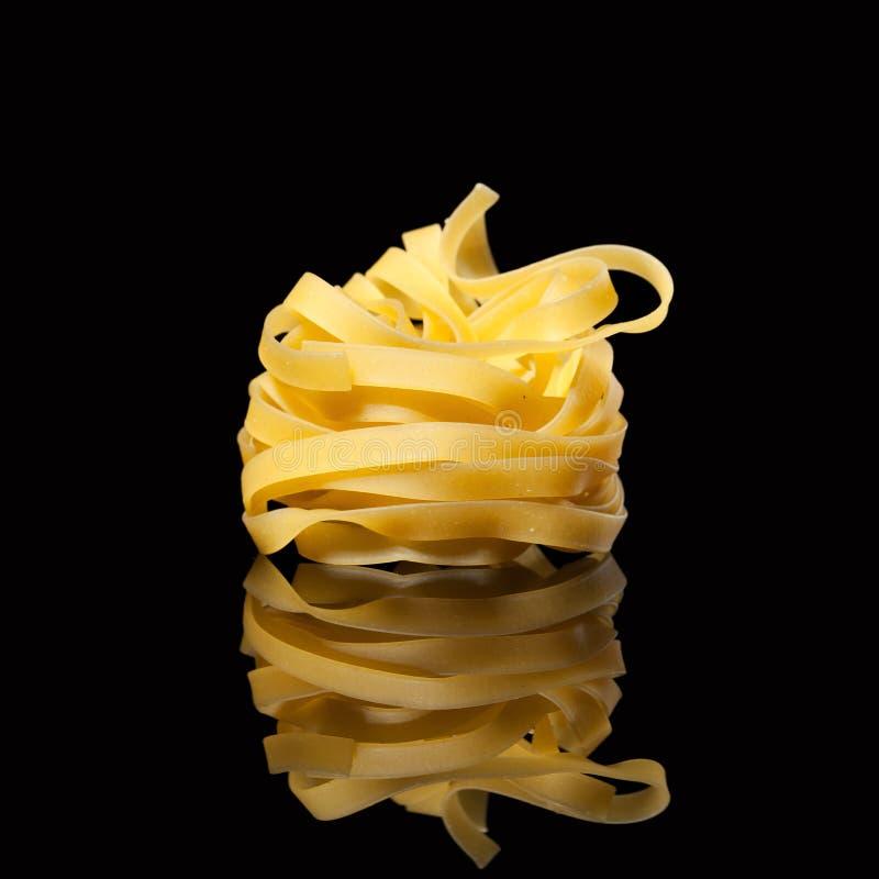 在黑背景的未加工的未煮过的tagliatelle巢与反射 传统意大利的意大利面食 免版税库存图片