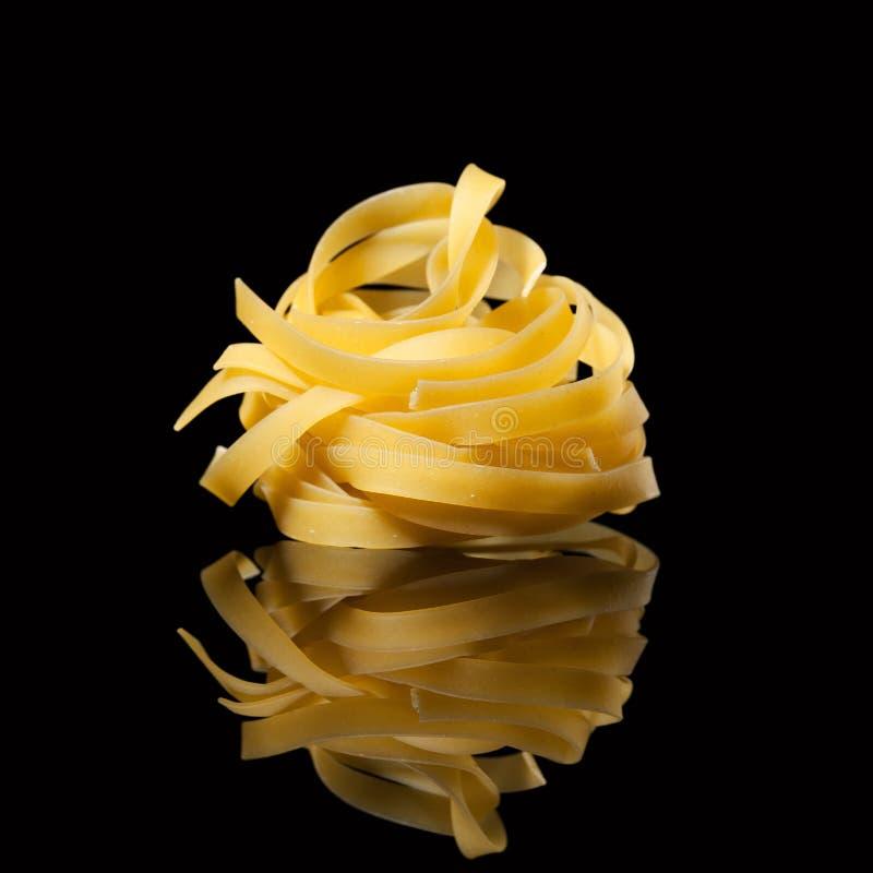 在黑背景的未加工的未煮过的tagliatelle巢与反射 传统意大利的意大利面食 免版税图库摄影