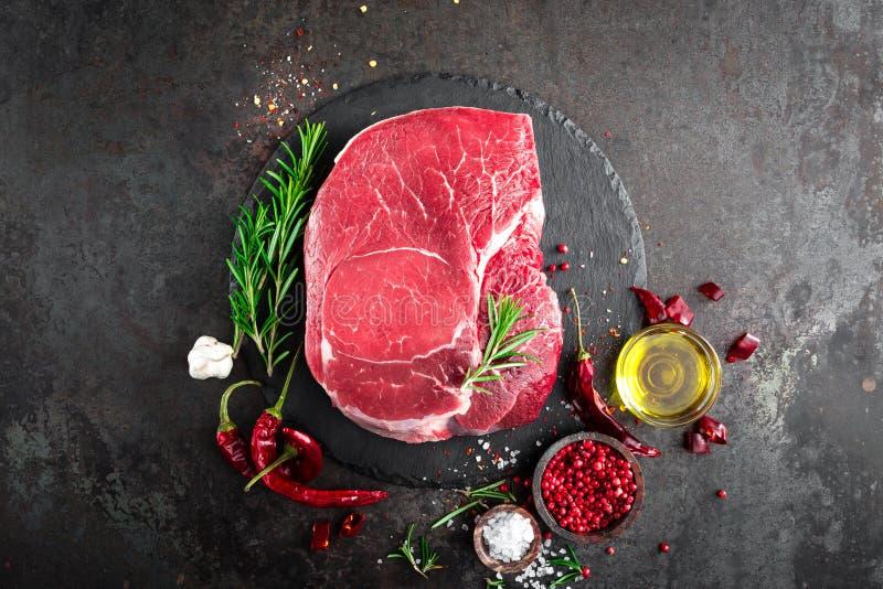 在黑背景的未加工的牛排与烹调成份 牛肉鲜肉 免版税库存图片