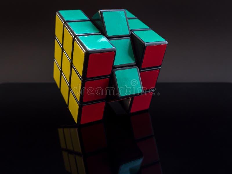 在黑背景的标准传统rubik ` s立方体与解决的反射 库存照片