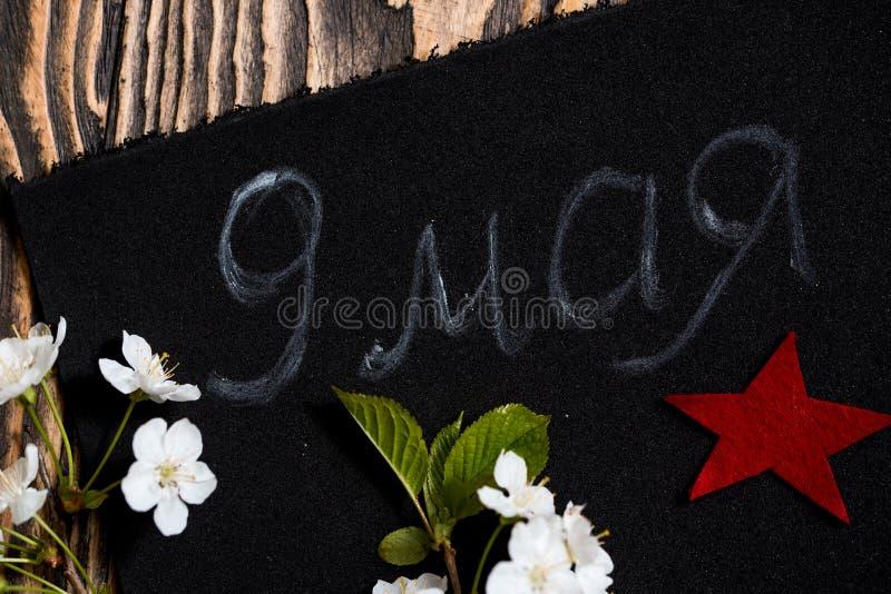 在黑背景的樱花5月9日, 红色星形 胜利的标志 荣誉5月9日 免版税库存照片