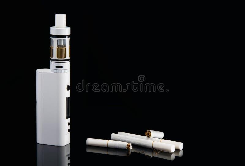 在黑背景的残破的香烟和在黑背景的一根现代电子香烟,与孵化 库存照片