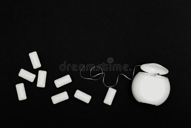 在黑背景的牙线和泡泡糖坐垫 库存图片