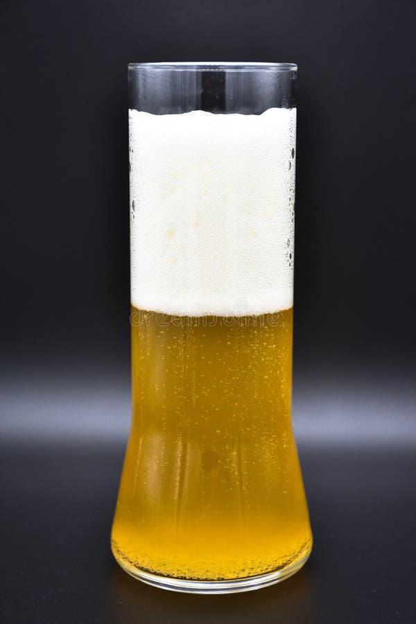 在黑背景的玻璃烧瓶与黄色液体和白色泡沫 图库摄影