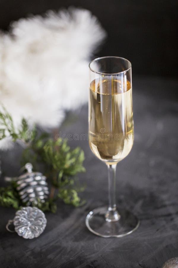 在黑背景的玻璃用与闪亮金属片的香槟和锥体 库存照片