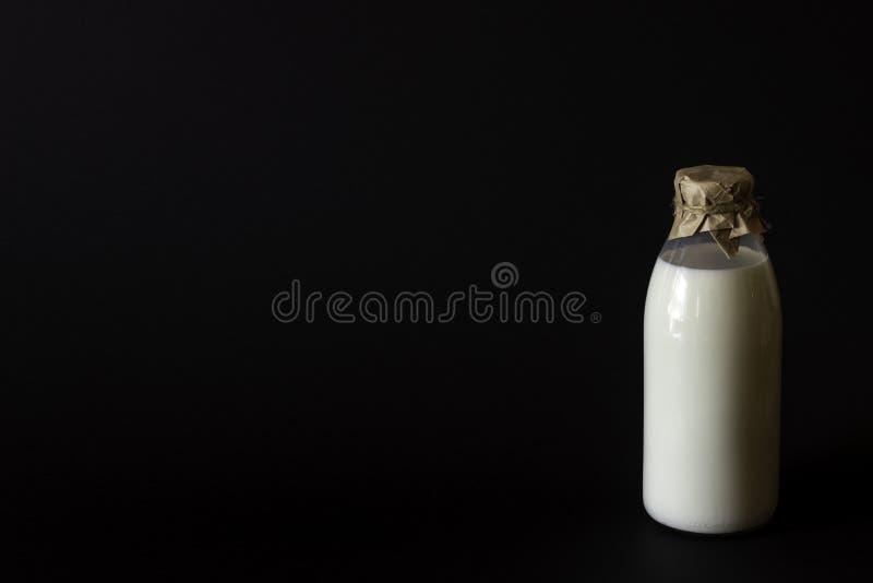 在黑背景的瓶牛奶 库存照片