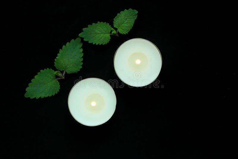 在黑背景的白色灼烧的tealight蜡烛 秀丽,温泉治疗,按摩疗法和放松概念 免版税图库摄影