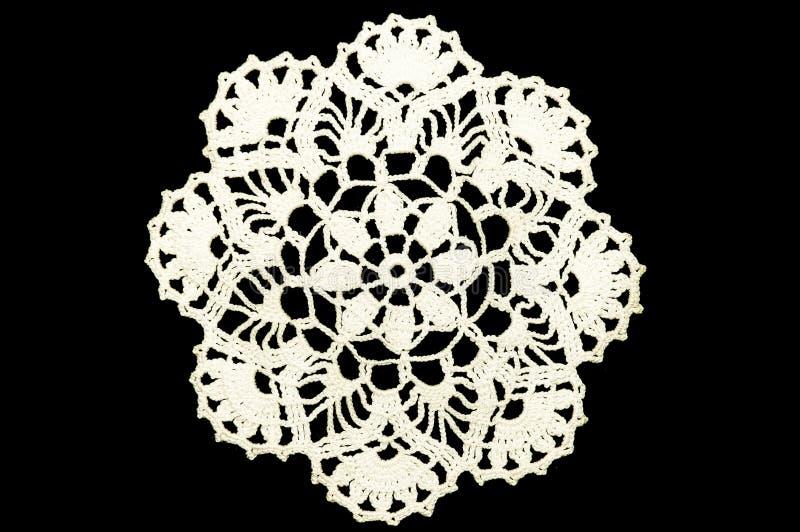 在黑背景的白色钩针编织的沿海航船鞋带小垫布 库存图片