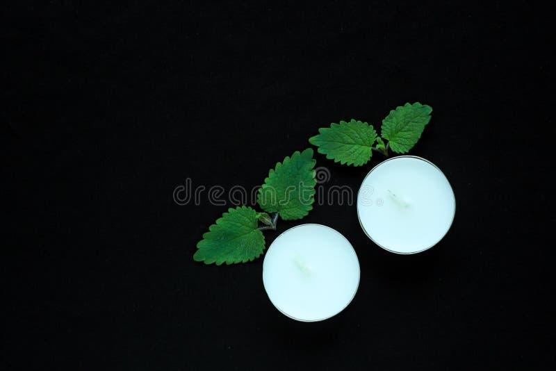 在黑背景的白色tealight蜡烛 秀丽,温泉治疗,按摩疗法和放松概念 库存图片