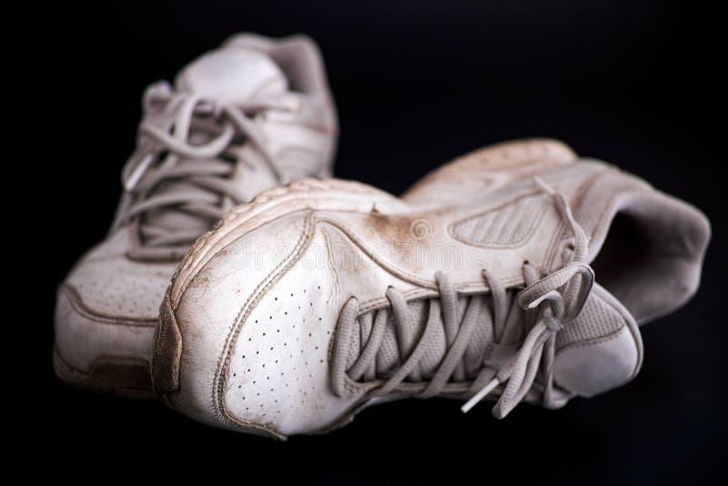 在黑背景的老肮脏的白色运动鞋 图库摄影