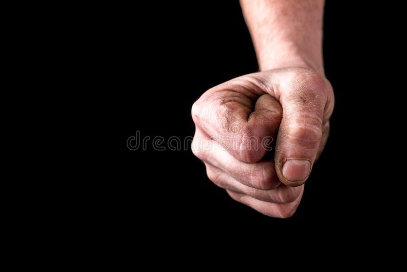 在黑背景的肮脏的拳头 免版税库存图片