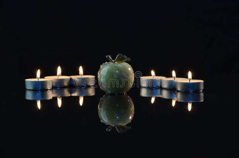 在黑背景的苹果计算机由烛光 库存图片