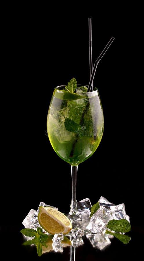在黑背景的酒精鸡尾酒用新鲜的夏天果子和冰块 图库摄影