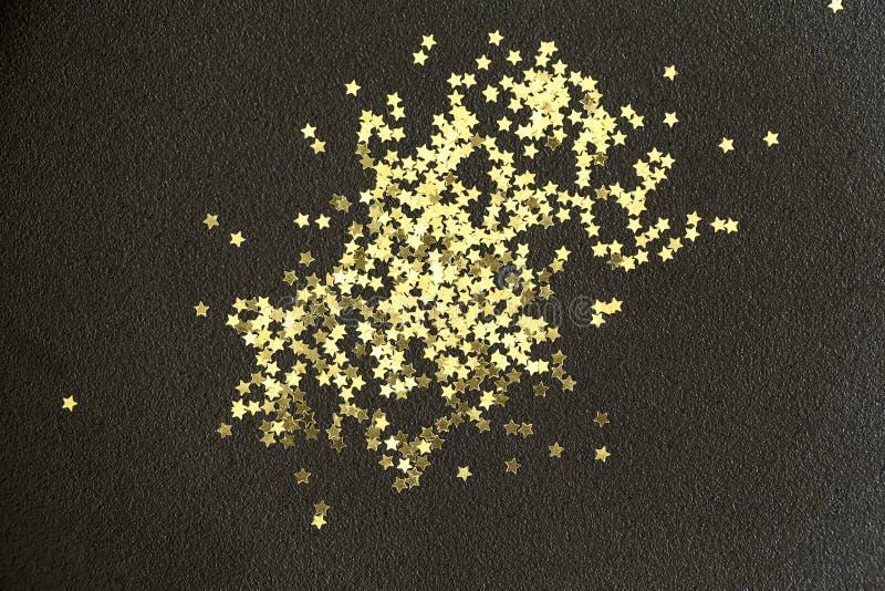 在黑背景的金黄圣诞节星 金黄闪烁纹理抽象背景 库存照片
