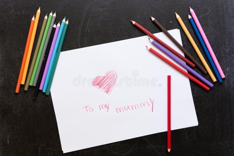在黑背景的铅笔画的白皮书的红心 铅笔 爱母亲节概念 对我的妈咪 免版税图库摄影