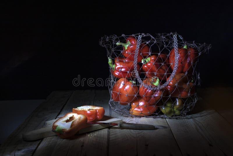 在黑背景的静物画 在金属篮子的红色甜椒 库存图片