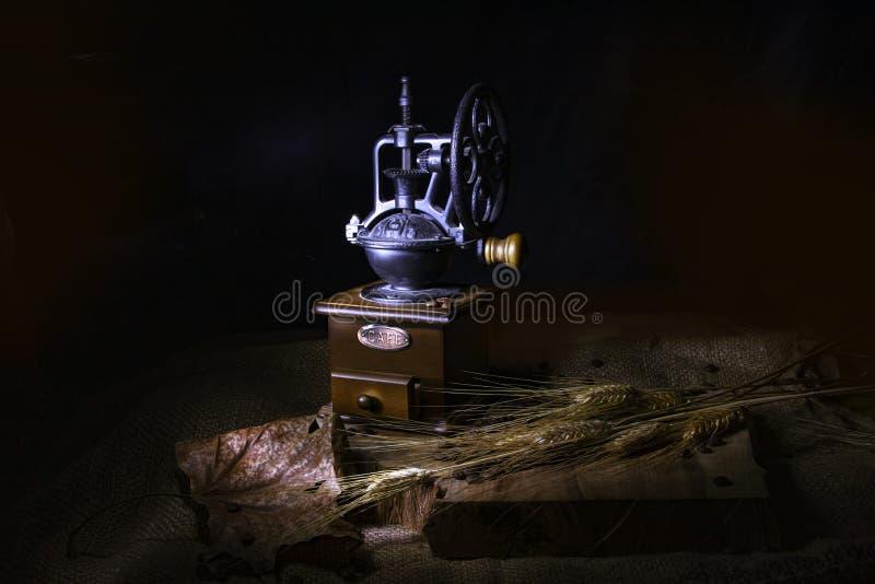 在黑背景的静物画 葡萄酒磨咖啡器、干燥麦子的叶子和耳朵在一张粗麻布隐蔽的木桌上的 图库摄影