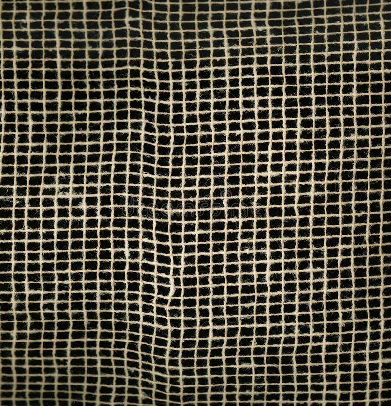 在黑背景的Textureof织品粗麻布帆布自然布朗滤网 宏观纹理样式背景 免版税库存图片