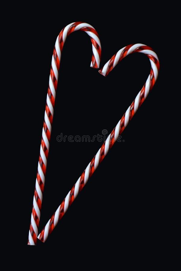 在黑背景贺卡动机的心形的红色和白色传统圣诞节棒棒糖 免版税图库摄影