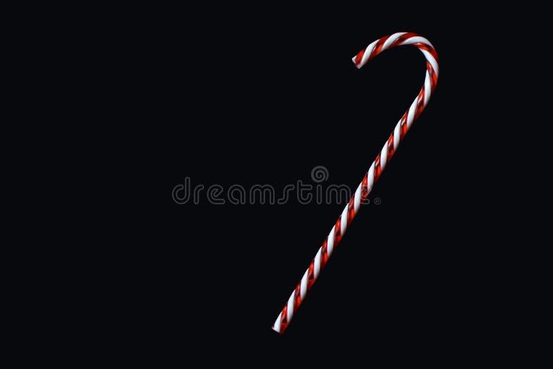 在黑背景贺卡动机的红色和白色传统圣诞节棒棒糖 免版税库存照片