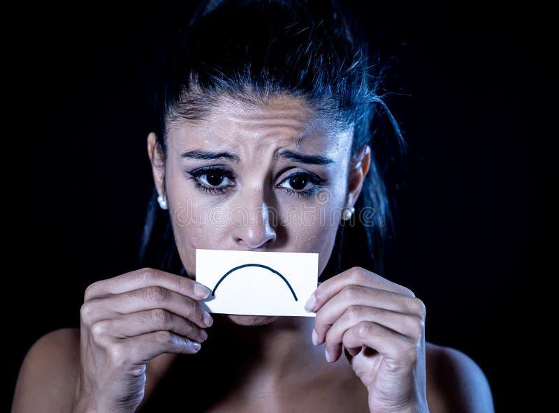 在黑背景遭受在剧烈的照明设备的消沉隔绝的哀伤的可爱的年轻拉丁妇女接近的画象 免版税图库摄影