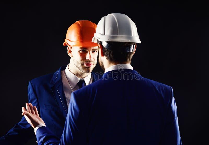 在黑背景隔绝的工程师 技术建筑师与有不满意的面孔的项目负责人谈话 工友 免版税图库摄影