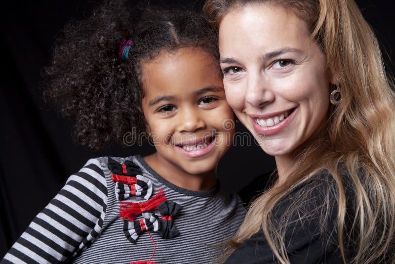 在黑背景隔绝的愉快的快乐的非洲家庭画象  图库摄影