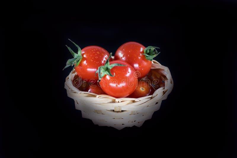 在黑背景隔绝的篮子的群蕃茄 库存图片