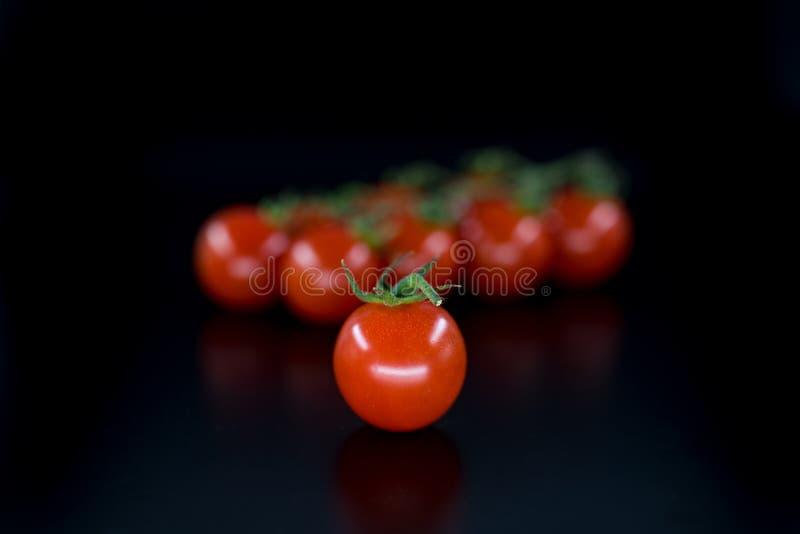 在黑背景隔绝的红色群蕃茄 免版税图库摄影