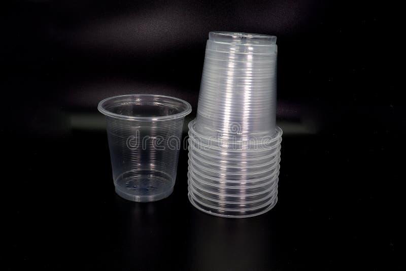 在黑背景隔绝的说谎的和站立的塑料杯子 免版税库存照片