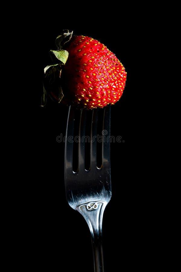 在黑背景隔绝的银色叉子的新鲜的草莓 r 库存图片