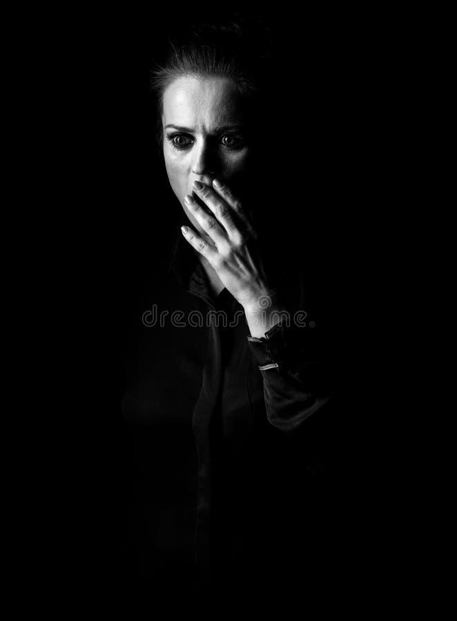 在黑背景隔绝的黑暗的礼服的被注重的妇女 库存图片