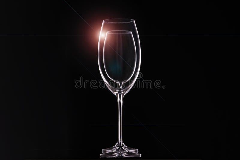 在黑背景,饮料的玻璃器皿的空的酒杯 等高和轻的强光,水平的安排 免版税图库摄影