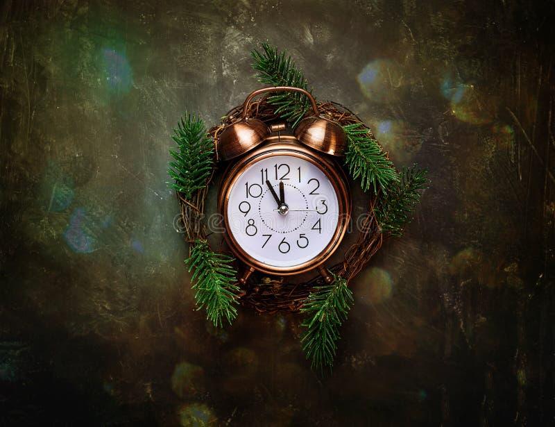 在黑背景Gli的葡萄酒铜闹钟五末日警钟毁灭・新生新年读秒圣诞节花圈杉树分支 免版税库存照片