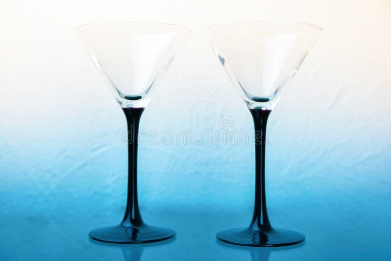 在黑腿的两块马蒂尼鸡尾酒玻璃在白蓝色背景 免版税库存图片