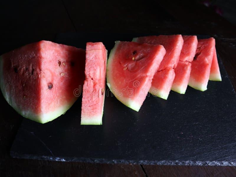 在黑色切的红色甜西瓜 库存照片