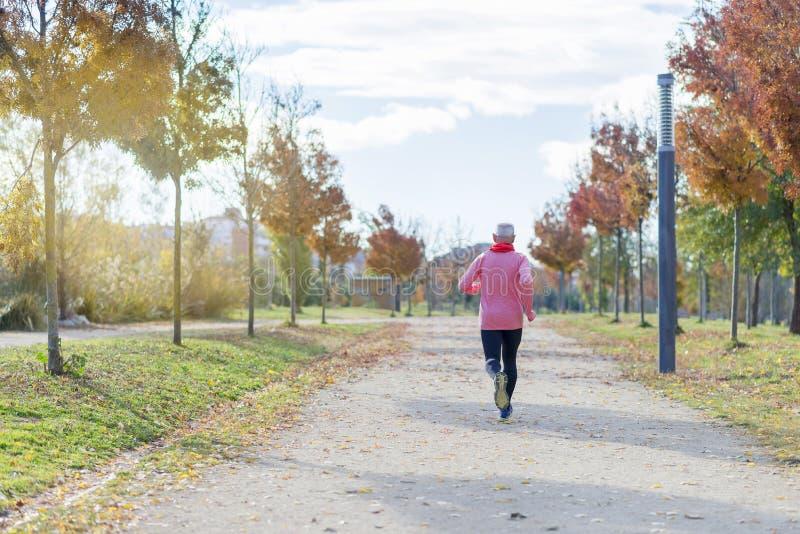 在黑色和绿色打扮的一名老人在公园跑 免版税库存照片