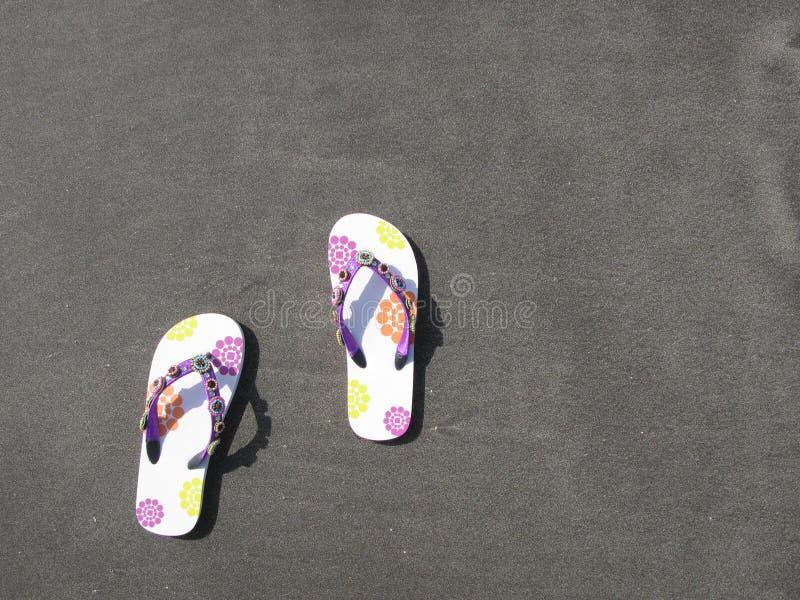 在黑色沙子的塑胶人字平底拖鞋 免版税库存照片