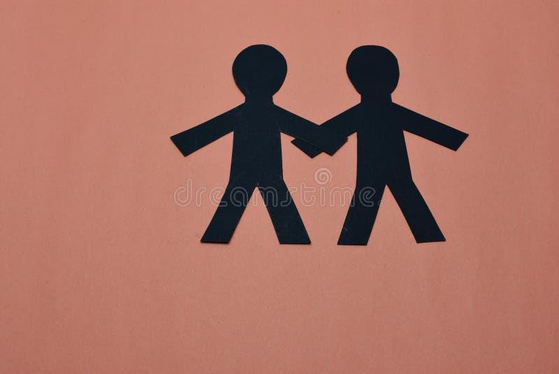 在黑色的两个男性剪影有橙色背景 免版税库存照片