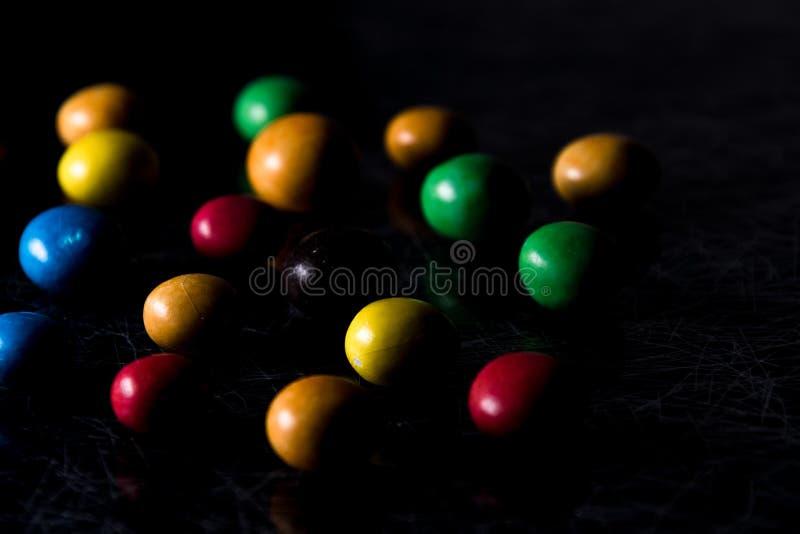 在黑色的几五颜六色,圆的巧克力糖和silv 库存图片