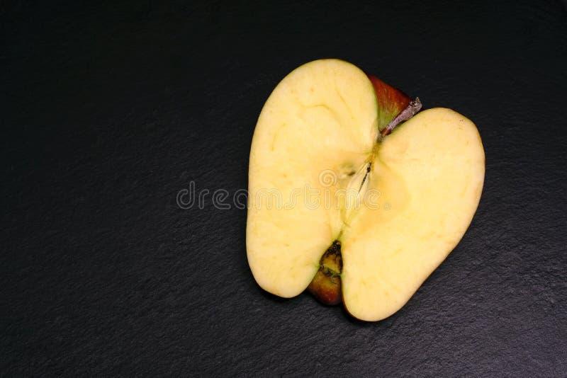 在黑色的切好的成熟苹果 免版税库存照片