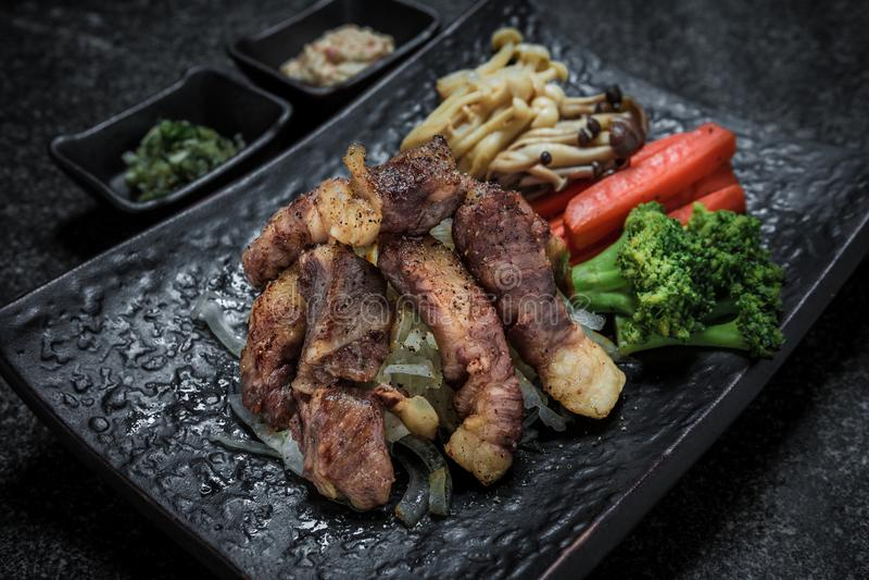 在黑色的盘子服务的烤肉日本食物裁减与菜 免版税图库摄影