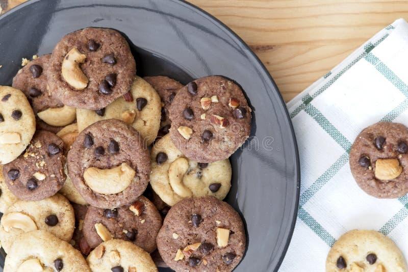 在黑色的盘子的可口巧克力曲奇饼,在木桌上的鲜美自创曲奇饼 免版税库存照片