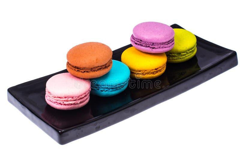 在黑色的盘子的多彩多姿的蛋白杏仁饼干 图库摄影
