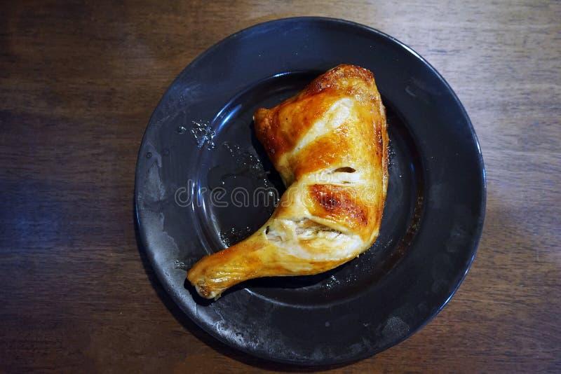在黑色的盘子的烤鸡腿 免版税库存照片
