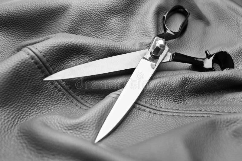 在黑色皮革背景的剪刀 库存照片