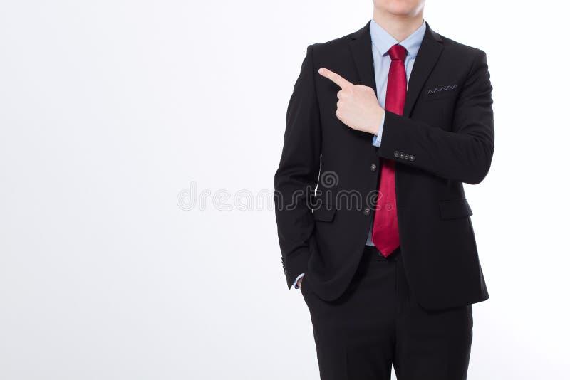 在黑衣服的商人指向由手指的隔绝在白色背景 复制空间并且嘲笑  到达天空的企业概念金黄回归键所有权 播种的图象 免版税图库摄影