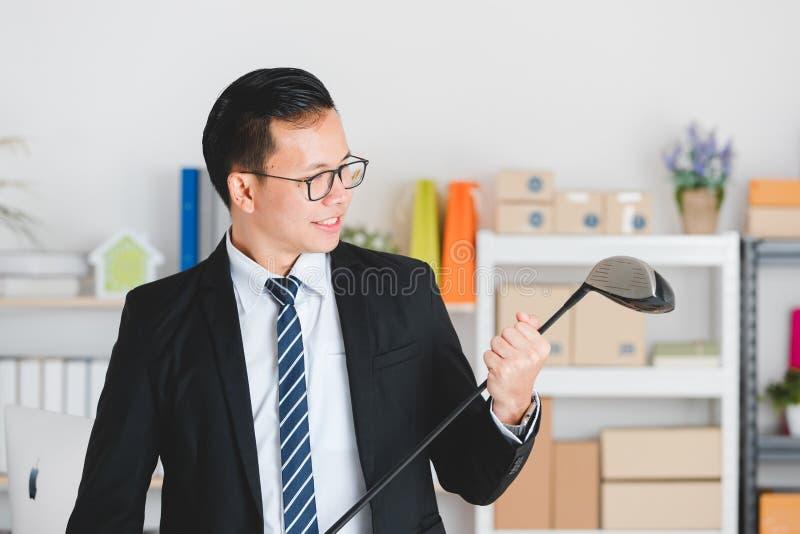 在黑衣服的年轻亚洲商人在办公室实践高尔夫球 免版税库存图片