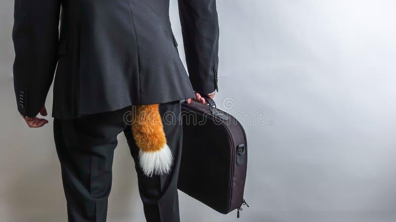 在黑衣服的鬼祟商人与公文包和狐狸尾巴 免版税库存照片