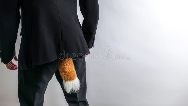 在黑衣服的鬼祟商人与狐狸尾巴 概念罪行,欺骗 库存图片